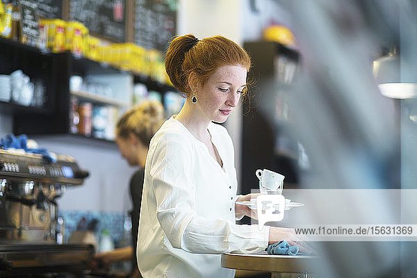 Junge Frau  die im Café arbeitet