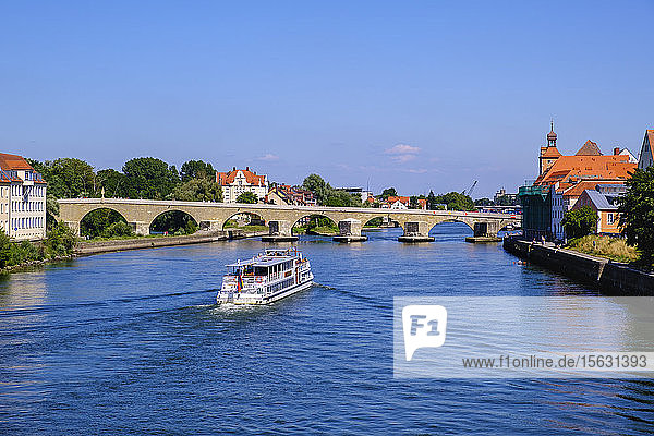 Excursion ship on Danube River with Stone Bridge in background against sky  Regensburg  Upper Palatinate  Bavaria  Germany