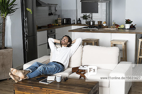 Relaxed man leaning back on couch at home