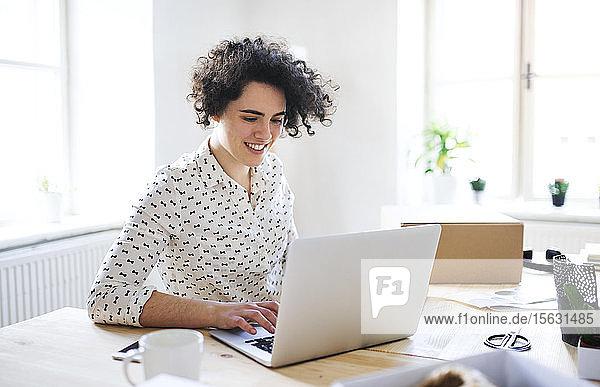 Lächelnde junge Frau arbeitet am Laptop am Schreibtisch