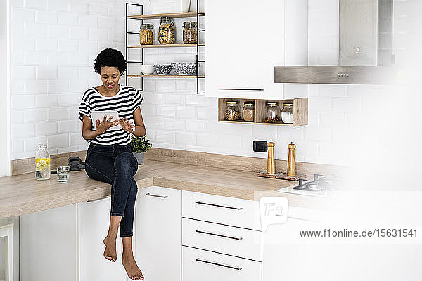 Young woman using tablet in kitchen at home
