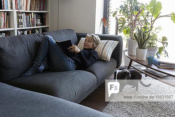 Reife Frau entspannt sich zu Hause auf der Couch und liest ein Buch
