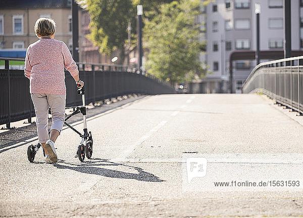 Ältere Frau mit Gehhilfe auf Rädern auf Fußgängerbrücke