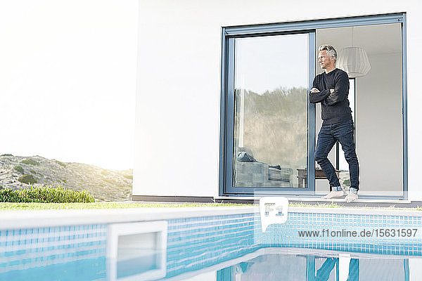 Smart man standing in front of his modern home with pool looking at the landscape