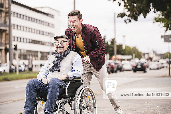 Laughing young man pushing happy senior man in wheelchair