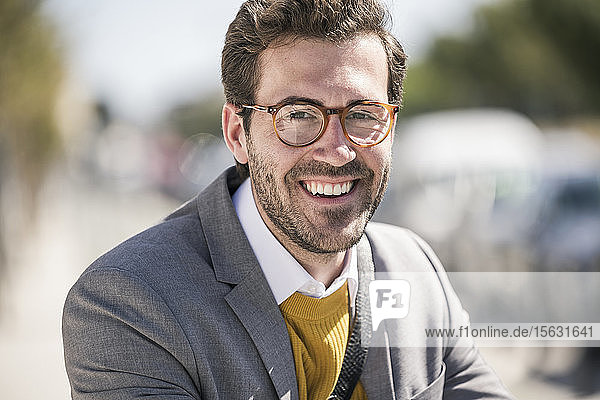 Portrait of smiling young businessman in the city
