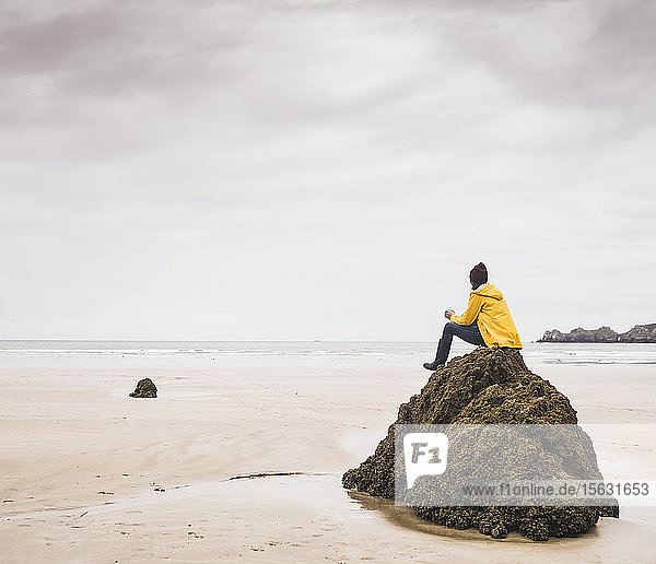 Young woman wearing yellow rain jacket sitting on rock at the beach  Bretagne  France