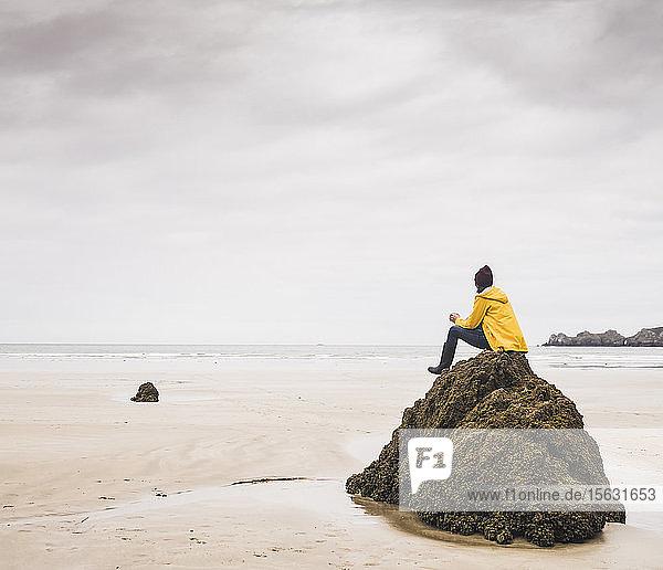 Junge Frau in gelber Regenjacke auf einem Felsen am Strand sitzend  Bretagne  Frankreich