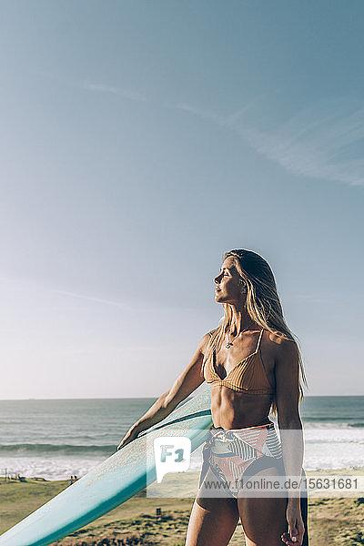 Junge blonde Surferin genießt das Sonnenlicht am Strand von Sopelana  Spanien