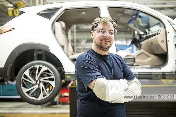 Porträt eines selbstbewussten Arbeiters in einer modernen Autofabrik