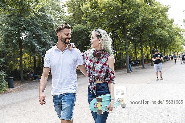 Glückliches junges Paar beim Spaziergang in einem Park