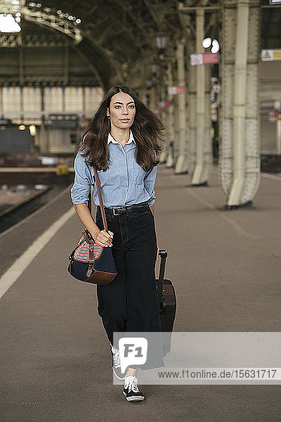 Young female traveller walking on train station