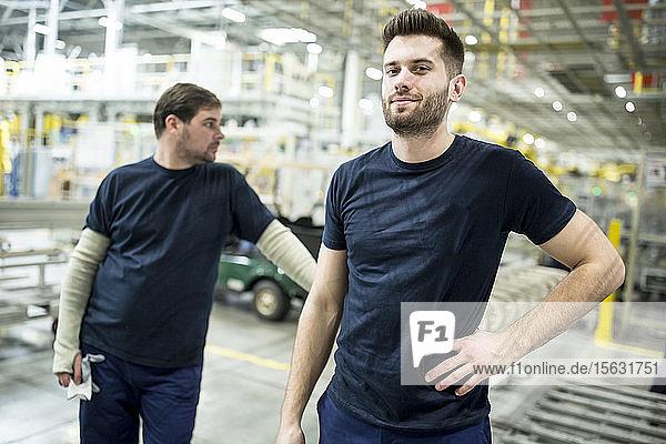 Zwei selbstbewusste Kollegen machen eine Pause in einer modernen Fabrik