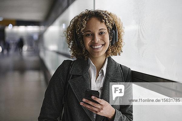 Porträt einer lächelnden Frau mit Kopfhörer und Smartphone