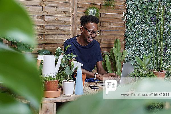 Lächelnder junger Mann mit Laptop auf seiner Terrasse