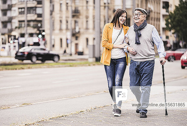 Adult granddaughter assisting her grandfather strolling with walking stick