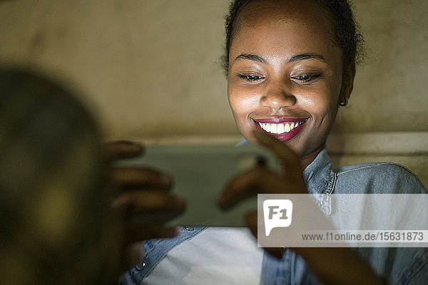 Porträt einer glücklichen jungen Frau  die nachts ein Smartphone benutzt  Lissabon  Portugal