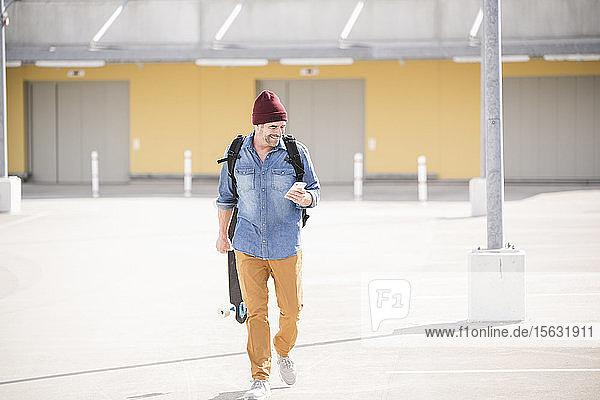 Lässiger reifer Mann mit Smartphone und Skateboard auf dem Parkdeck