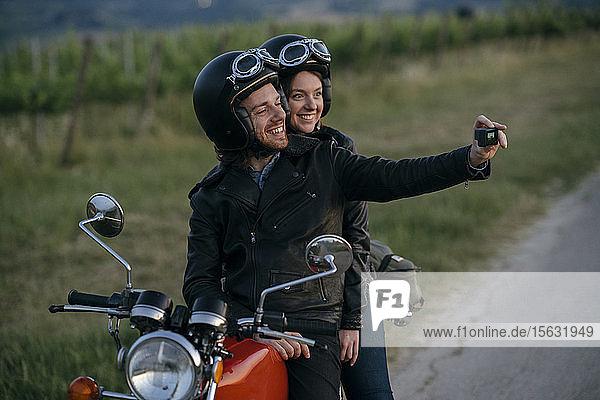 Porträt eines glücklichen jungen Paares auf einem Oldtimer-Motorrad  das sich am Straßenrand ein Selfie gönnt