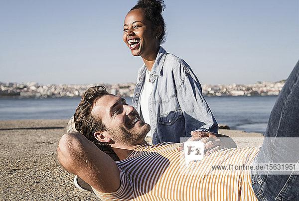 Glückliches junges Paar am Pier am Wasser liegend  Lissabon  Portugal