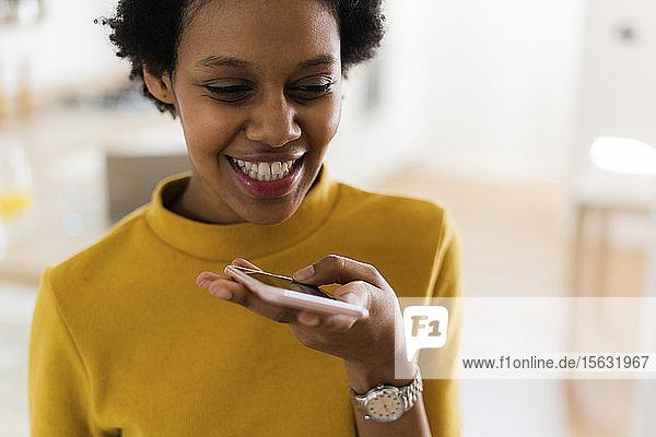 Glückliche junge Frau benutzt Smartphone zu Hause
