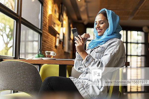Junge Frau trägt einen türkisfarbenen Hijab und benutzt ein Smartphone in einem Cafe