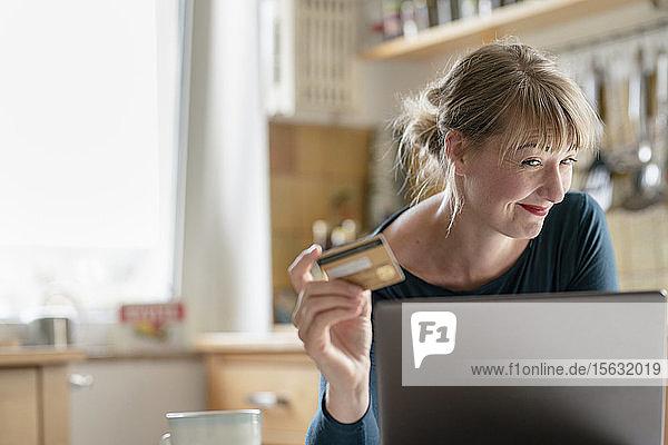 Lächelnde Frau in der Küche mit Kreditkarte und Laptop