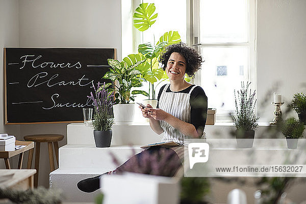 Portrait of smiling young woman using cell phone in a small shop with plants