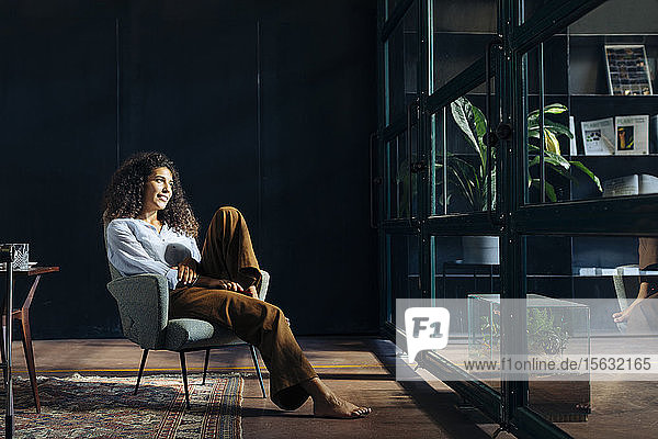 Young businesswoman looking out of window in loft office