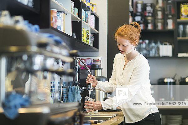 Junge Frau  die im Café arbeitet und Geschirr spült