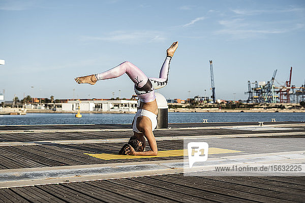 Asiatin  die auf einem Pier im Hafen Yoga praktiziert  Kopfstand mit Spalt