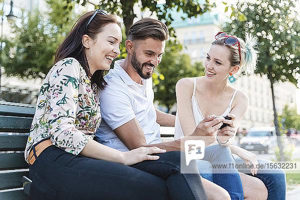 Drei Freunde sitzen zusammen auf einer Bank und schauen auf ihr Handy