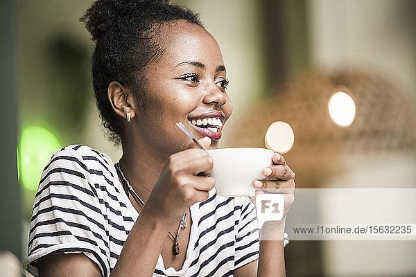 Porträt einer glücklichen jungen Frau  die in einem Café eine Kaffeetasse hält