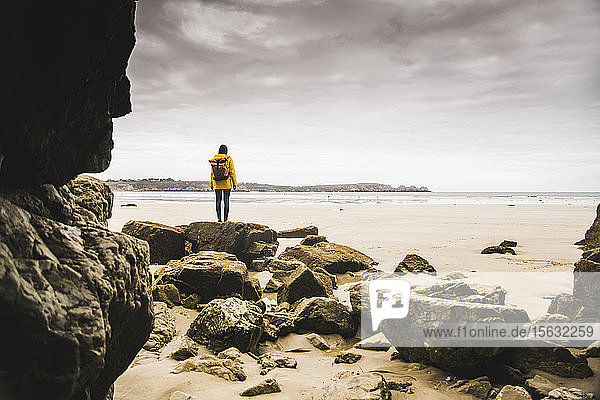 Junge Frau in gelber Regenjacke am Strand der Felshöhle  Bretagne  Frankreich