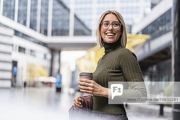 Glückliche junge Frau mit Kaffee zum Mitnehmen in der Stadt