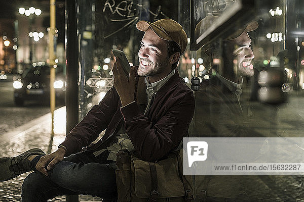 Porträt eines glücklichen jungen Mannes am Telefon  der nachts an einer Bushaltestelle sitzt  Lissabon  Portugal