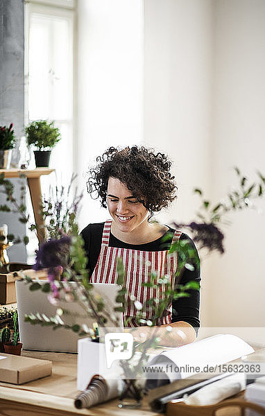 Smiling young woman using laptop in a small shop with plants