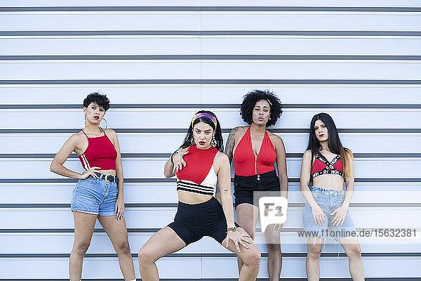 Vier junge sexy Tänzer tanzen auf einer Strett vor einer Wand