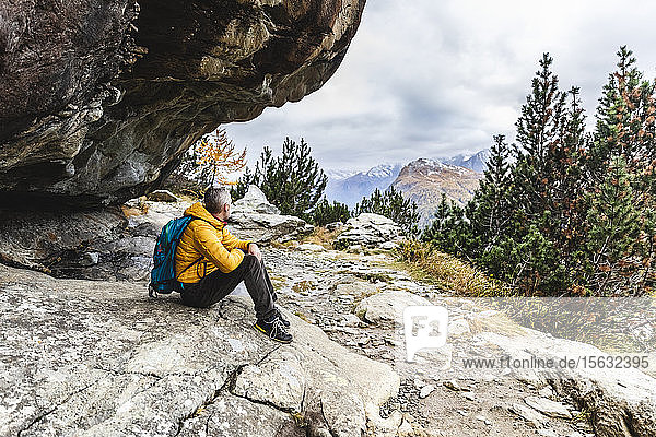 Wanderer sitzt und blickt im Herbst über das Alpenplateau  Sondrio  Italien
