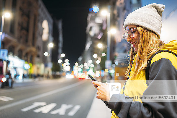 Smiling young woman in the city using her smartphone at night