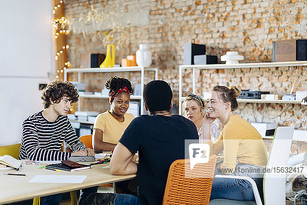 Young people sitting together at table and talking