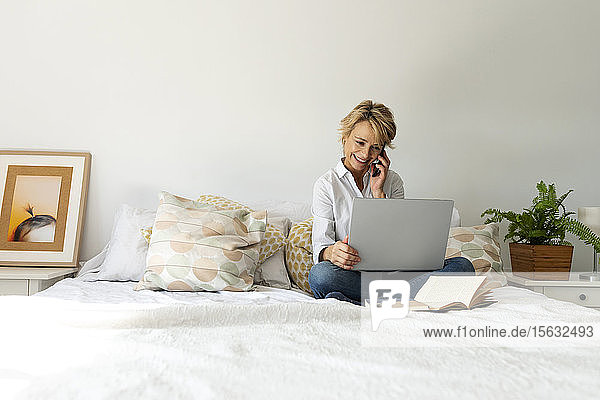 Mature woman sitting on bed at home using smartphone and laptop