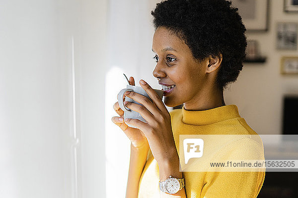 Smiling young woman drinking from mug at home