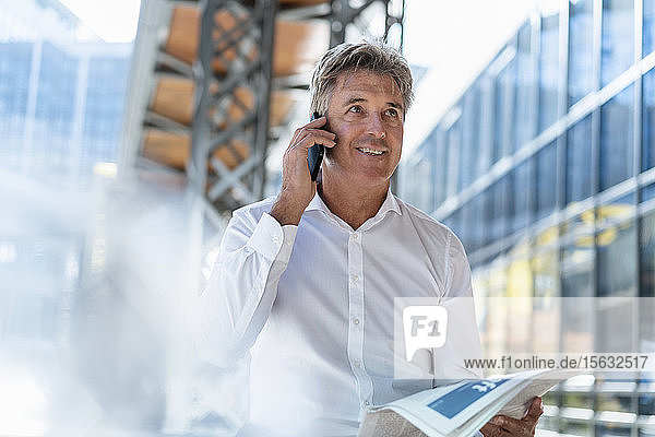Reifer Geschäftsmann mit Zeitung am Telefon in der Stadt