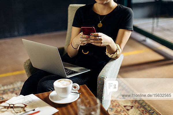 Close-up of young businesswoman with laptop and smartphone in loft office