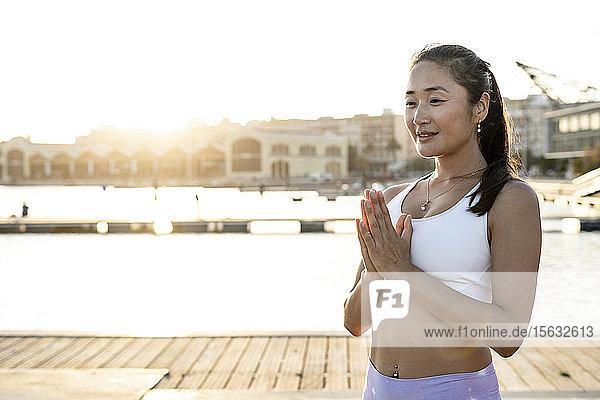 Asiatische Frau beim abendlichen Yoga am Hafen Asiatische Frau beim abendlichen Yoga am Hafen