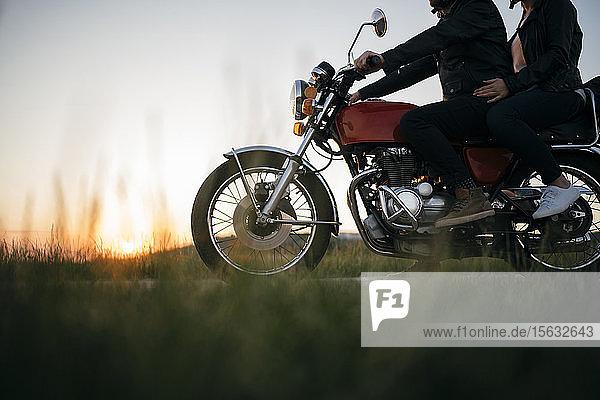 Schnappschuss eines Paares auf einem Oldtimer-Motorrad bei Sonnenuntergang
