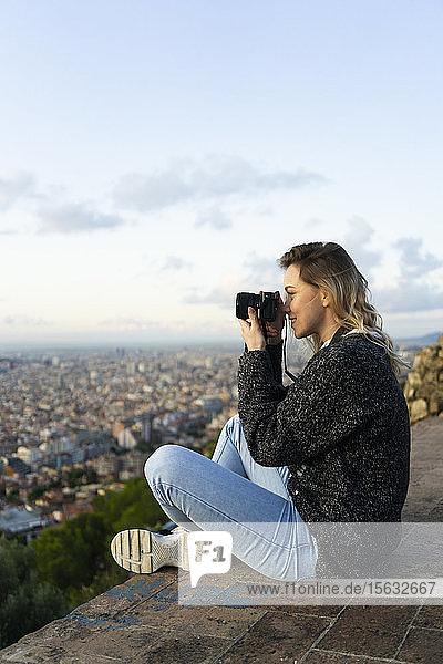 Junge Frau fotografiert bei Sonnenaufgang über der Stadt  Barcelona  Spanien