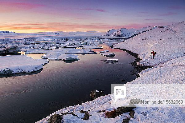 Touristen fotografieren  während sie bei Sonnenuntergang an der Lagune Jokulsarlon gegen den Himmel stehen  Island