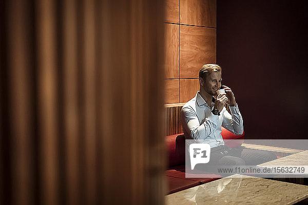 Geschäftsmann sitzt in einer Lounge  trinkt einen Kaffee und benutzt ein Smartphone